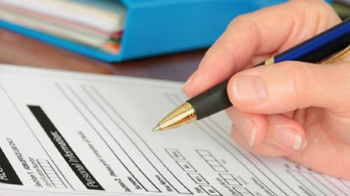 A hand holding a pen to an application form