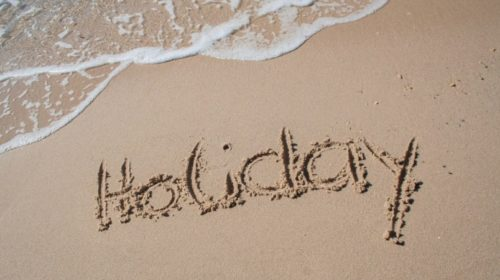 """The word """"holiday"""" written in sand on a beach"""