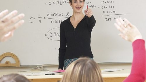Teacher standing at whiteboard with class in front