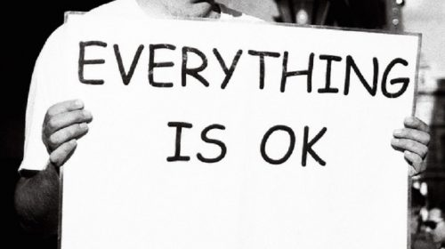 "Person holding a signing saying ""Everything is OK"""