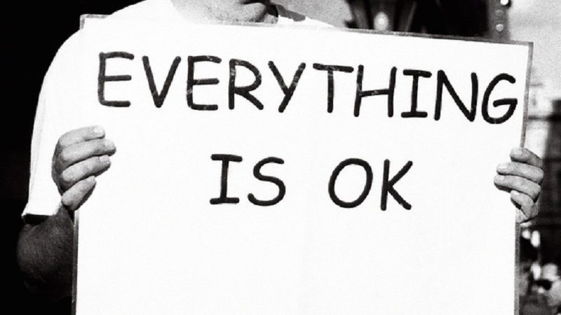 """Person holding a signing saying """"Everything is OK"""""""
