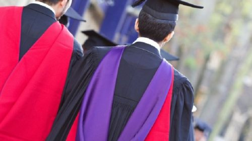 Two graduands seen from behind in gowns