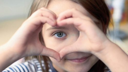 Small child making a heart sign